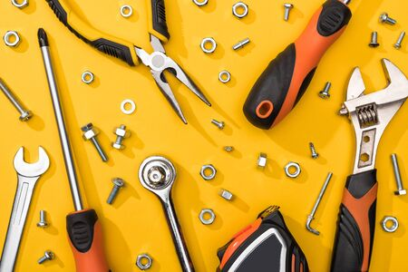Top view of tool set with nuts and wood screws on yellow background
