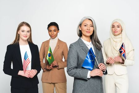 multicultural businesswomen with flags of different countries isolated on white