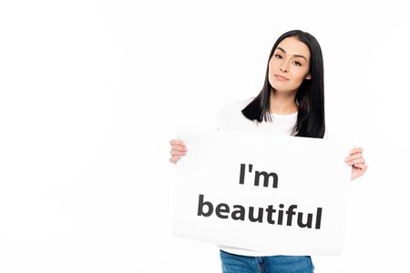 attractive woman looking at camera while holding poster with i`m beautiful lettering isolated on white