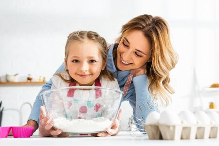 Selective focus of happy mom and cute daughter holding bowl with flour in kitchen