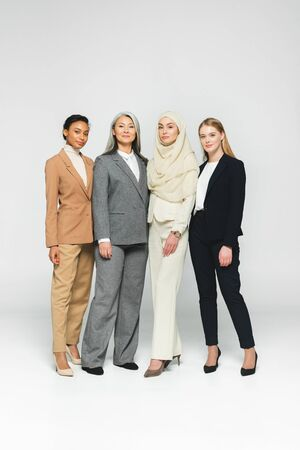 beautiful multicultural businesswomen standing on white