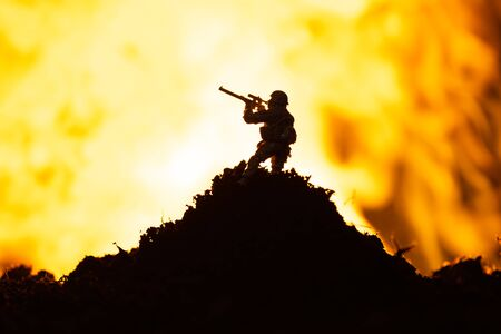 Battle scene with toy warrior on battleground and fire at background Stock fotó