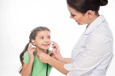 Smiling pediatrician giving stethoscope to smiling kid isolated on white Stock fotó