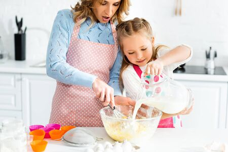 cropped view of mother cooking with balloon whisk and daughter pouring milk Reklamní fotografie