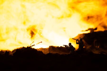 Battle scene with toy soldiers and tank on battleground with fire at background