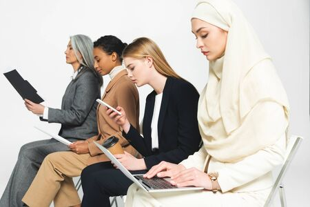 side view of multicultural businesswomen sitting on chairs with gadgets isolated on white
