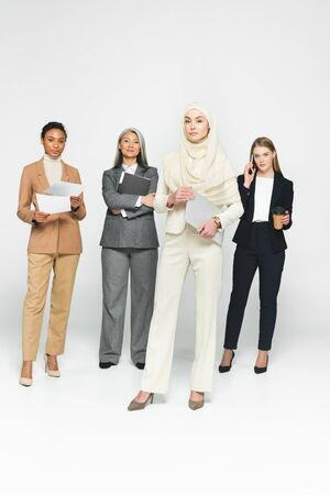 attractive multicultural businesswomen near arabian woman with laptop on white