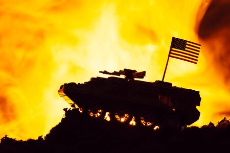 Battle scene with american flag on toy tank and fire at background
