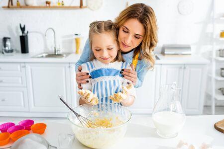 smiling mother hugging cute daughter during cooking dough Reklamní fotografie