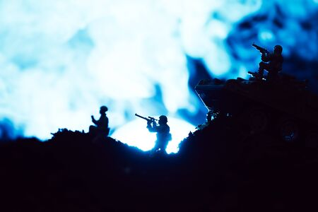 Battle scene with toy soldiers and smoke with moon on black background