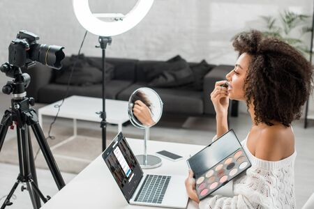 KYIV, UKRAINE - DECEMBER 10, 2019: side view of african american influencer holding eye shadow palette near laptop with linkedin website and digital camera