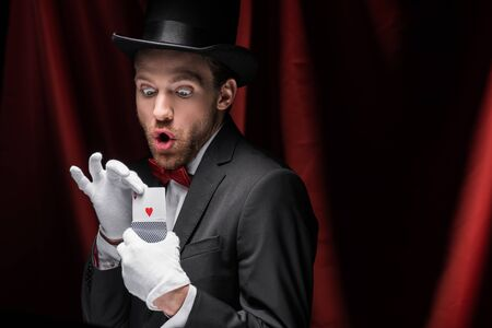 KYIV, UKRAINE - NOVEMBER 27, 2019:shocked magician holding playing cards in circus with red curtains
