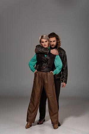 man in leather jacket hugging woman in vest on grey background Standard-Bild