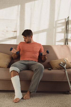 Handsome man with broken leg training with dumbbells on sofa at home Stockfoto