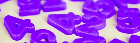 Panoramic shot of purple plastic numbers on white surface Stock fotó