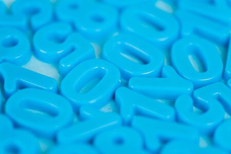 Selective focus of plastic numbers on blue background