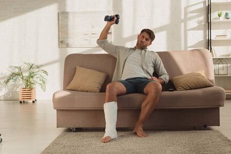 Man with broken leg sitting on couch and training with dumbbells at home Stockfoto