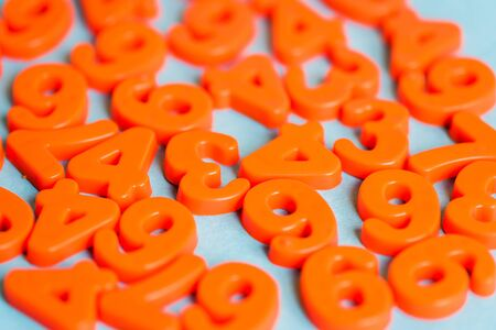 Selective focus of orange plastic numbers on blue background