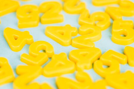 Selective focus of yellow plastic numbers on blue background Imagens