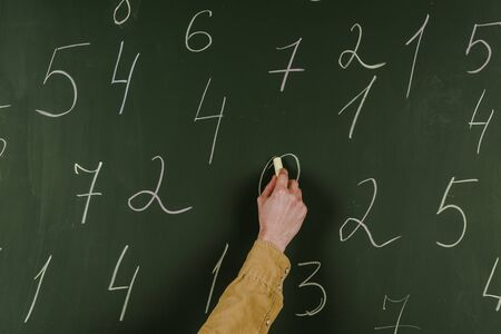 Cropped view of man writing numbers with chalk on blackboard