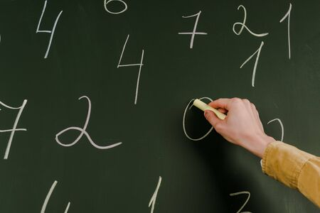 Cropped view of man with chalk writing numbers on blackboard