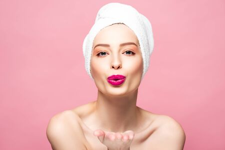 happy woman in white towel sending air kiss isolated on pink