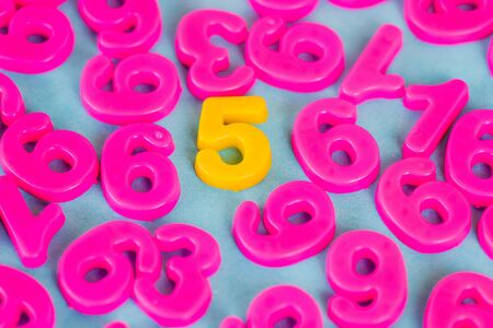 Yellow five number and pink plastic numbers on blue background