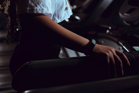 Cropped view of african american woman holding treadmill by hand with smart watch