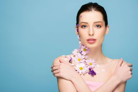 attractive woman with flowers and crossed arms isolated on blue
