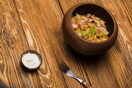 delicious varenyky with cracklings in bowl served with sour cream on wooden table