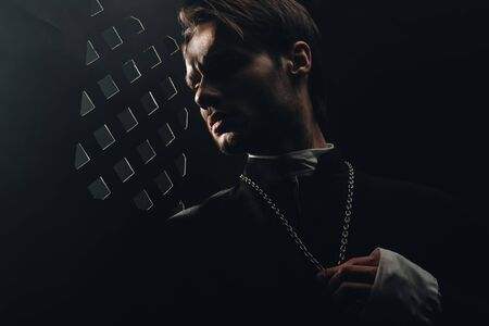 young serious catholic priest touching cross on his necklace in dark near confessional grille Zdjęcie Seryjne