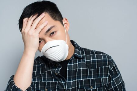 young asian man in respirator mask touching forehead and looking at camera while suffering from headache isolated on grey Archivio Fotografico