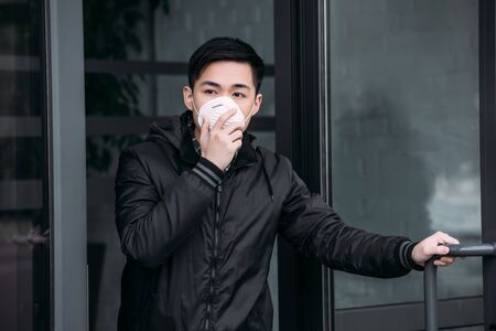 young asian man touching respirator mask while going out of building and looking away Stock Photo