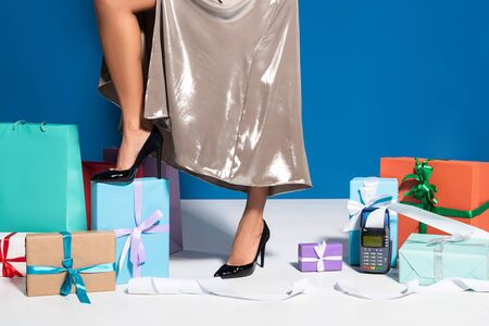 cropped view of african american woman in silver dress near payment terminal with check, shopping bags and gifts on blue background Imagens