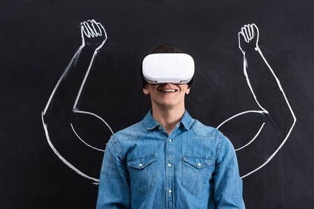 happy young man using virtual reality headset, with muscular arms drawing on blackboard