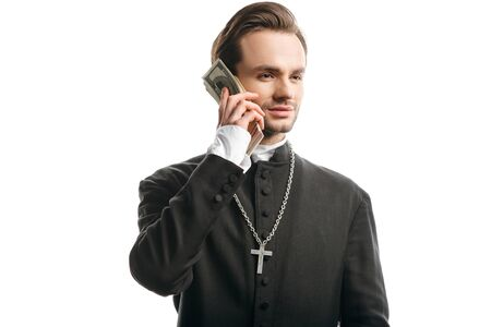 corrupt catholic priest looking away while holding money near face isolated on white