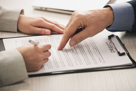 cropped view of realtor pointing with finger at clipboard with contract lettering near woman