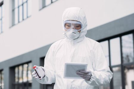 asian epidemiologist in hazmat suit and respirator mask using digital tablet while holding test tube with blood sample on street