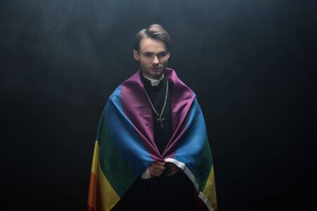 serious catholic priest wrapped in lgbt flag while looking at camera on black background with smoke