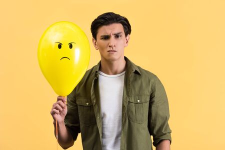 skeptical young man holding angry balloon, isolated on yellow