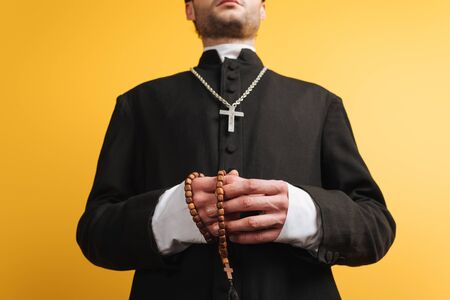 low angle view of catholic priest holding wooden rosary beads isolated on yellow