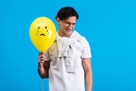 sad young man holding yellow crying balloon, isolated on blue