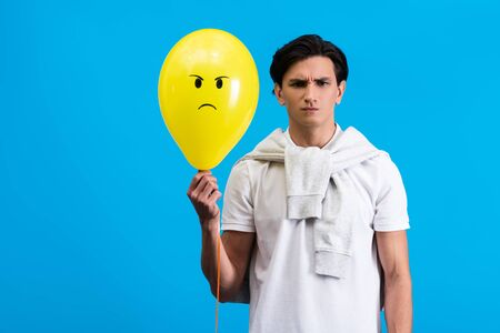 angry young man holding yellow balloon, isolated on blue Фото со стока