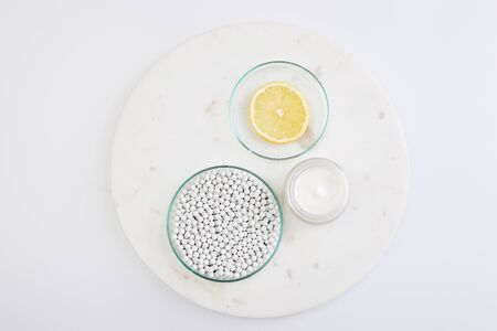 Top view of laboratory glassware with decorative beads, slice of lemon next to cosmetic cream on round stand on white background
