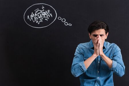 frightened young man with thought bubble drawing on blackboard Stock Photo