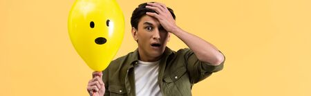 panoramic shot of worried man holding shocked balloon, isolated on yellow Фото со стока