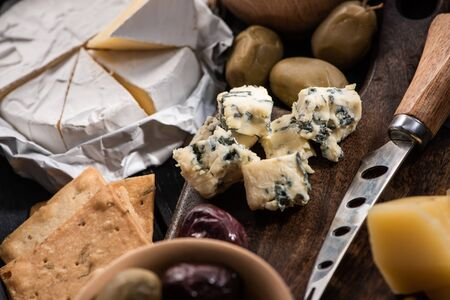 Selective focus of dorblu with knife, grana padano and olives on cutting board next to camembert and crackers Stock fotó