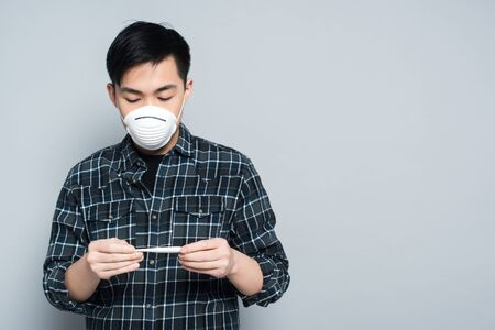 young asian man in respirator mask looking at thermometer on grey background