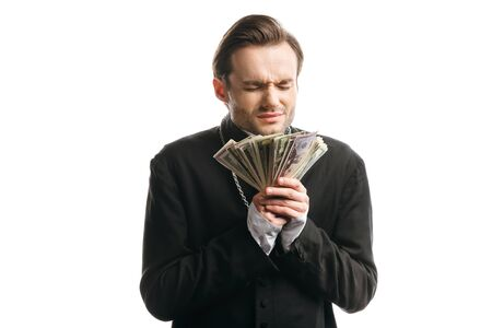 corrupt catholic priest with closed eyes holding dollar banknotes isolated on white Stock Photo