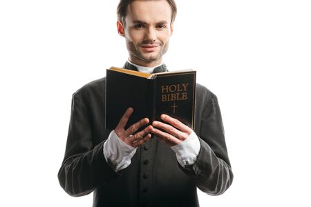 young, smiling catholic priest holding holy bible while looking at camera isolated on white